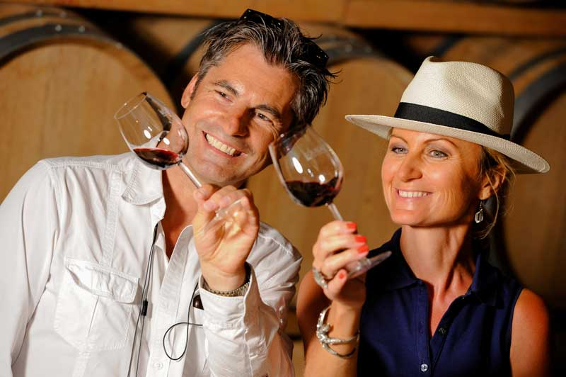 A man and woman tilting their wine glass to see the streaks on the glass and judge the quality of the wine.